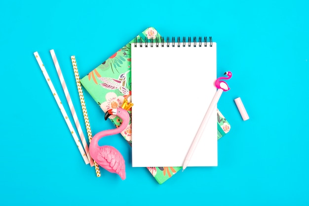 Notebook, pen, flamingo figure, drinking paper straws on blue background