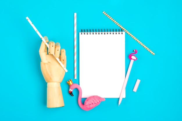 Notebook, pen, flamingo figure, smartphone, candle, drinking paper straws on blue background