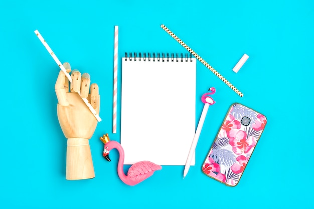 Notebook, pen, flamingo figure, smartphone, wooden hand hold drinking paper straws on blue background