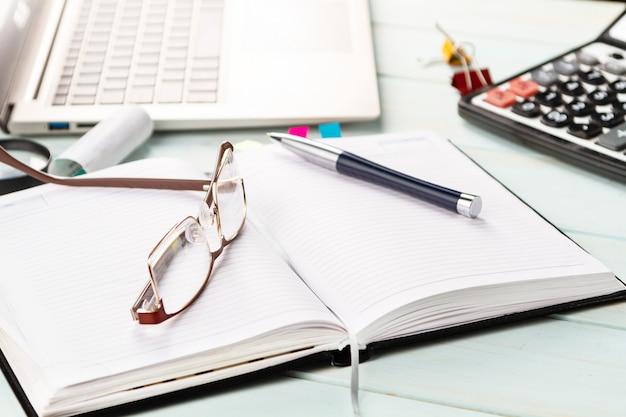 Блокнот, ручка, очки, финансовые документы на столе.