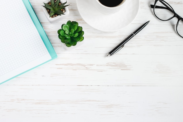 Notebook, pen, glasses, plants succulents, a cup of coffee on a white wooden table, flat lay, top view. office table desk, workplace