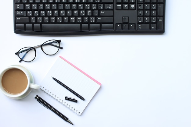 Notebook,pen,keyboard and coffee mug placed on a white desk.