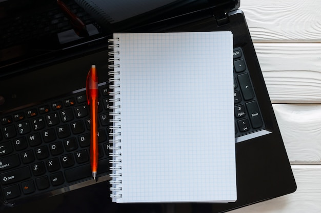 Notebook and pen lying on a laptop keyboard