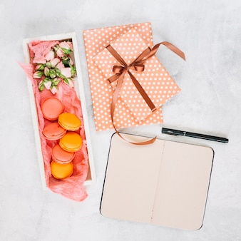 Notebook and pen near dessert and presents