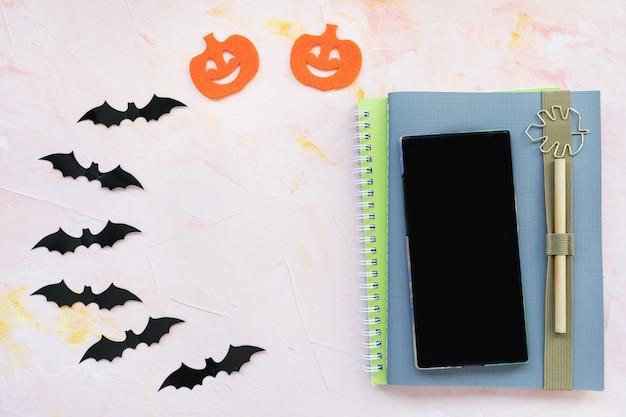 Notebook, pen, pumpkin, bats and a phone background