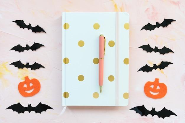 ピンクの背景のハロウィーンのコンセプトのノートブックペンカボチャとコウモリ