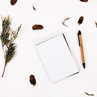 Notebook between pen and twig