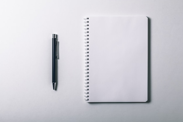 Notebook and pen on white background.