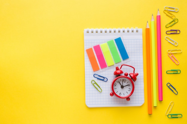 Notebook, pencil and colored paper clips, clock alarm on yellow