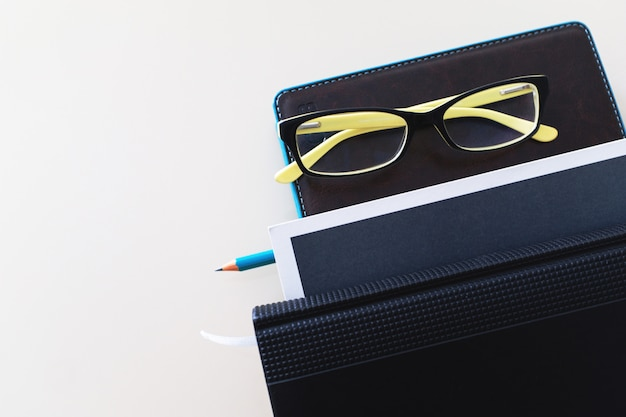 Notebook, pencil, glasses and a stack of books.