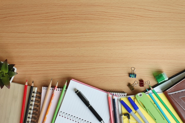 Notebook, pencil, pen and equipment placed on a brown wooden floor.