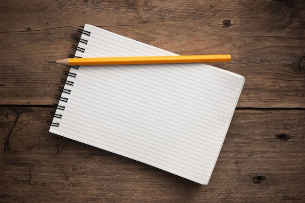 Notebook and  pencil on a wooden background