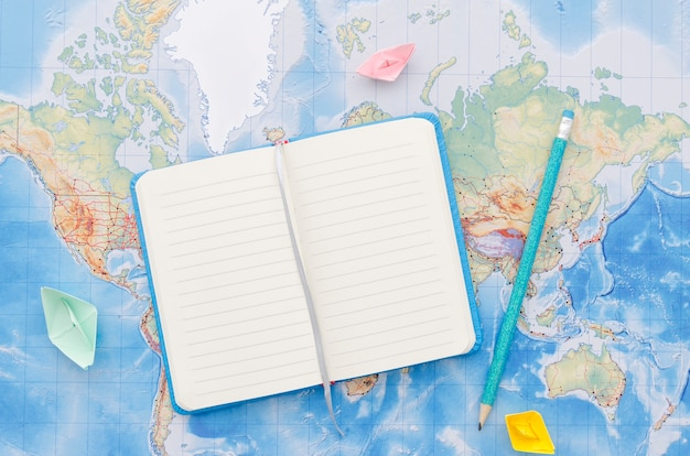 Notebook and pencil on world map