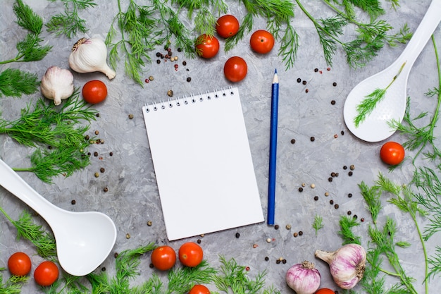 Notebook and pencil for writing recipes surrounded by cherry, dill, pepper spice, garlic and ladles on a gray background.