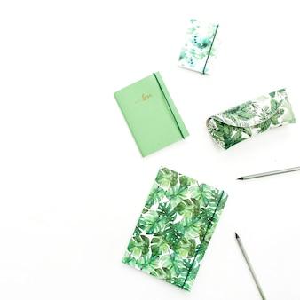 Блокнот, карандаши и пенал в стиле экзотической тропической пальмы на белой поверхности