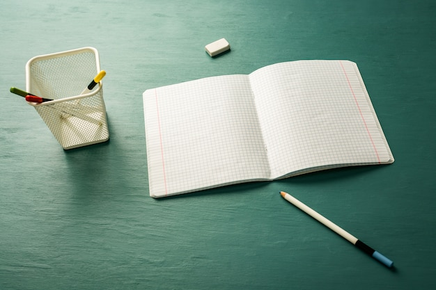 Notebook and pencils on the green table