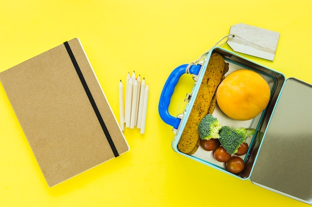 Notebook and pencils near opened lunchbox