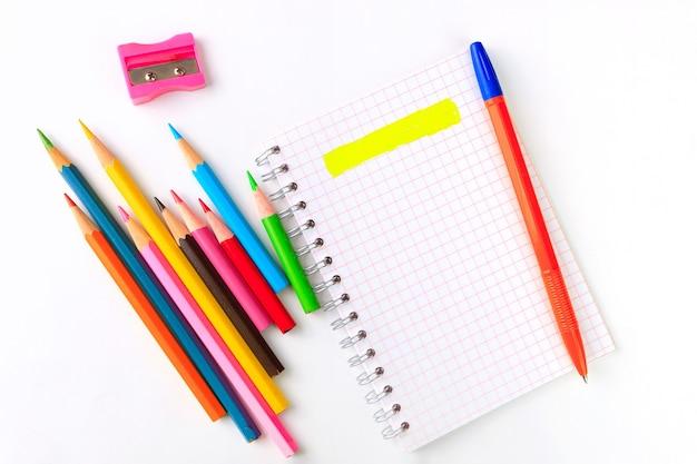 白のノート、ペン、色とりどりのマーカー