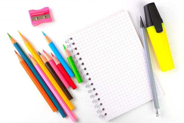 Notebook, pens and markers on a white background, stationery writing supplies