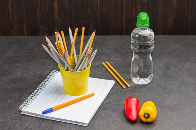 Notebook and pens, peppers and bottle of water