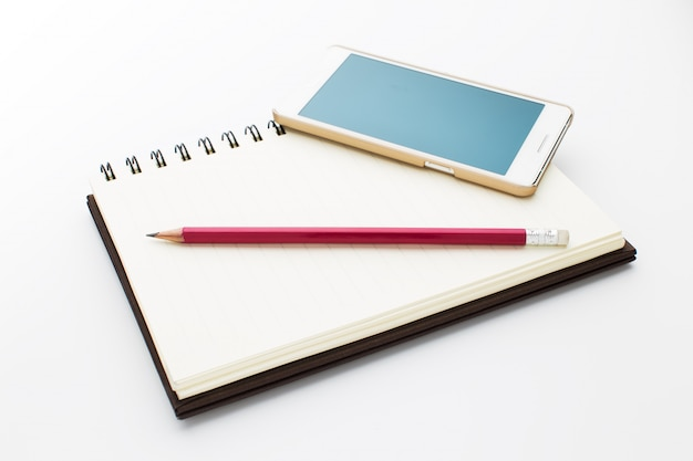 Notebook, phone and pencil isolated on white background.