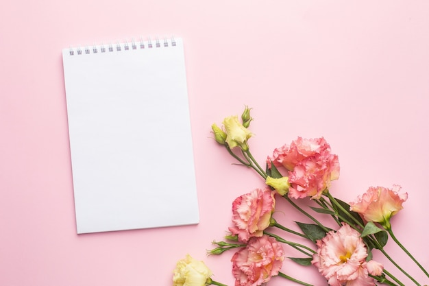 Notebook and pink flower bouquet on pastel background