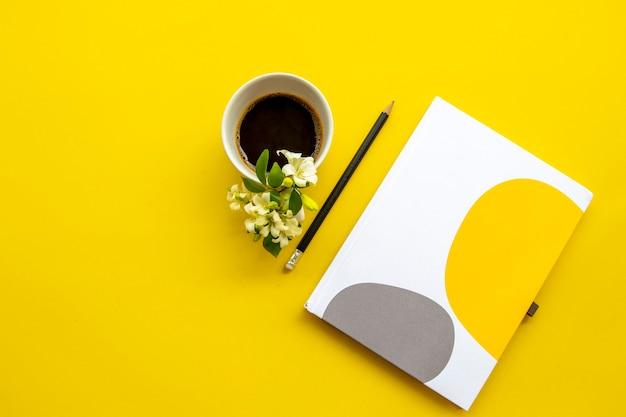 黄色のコーヒーとノートブックプランナー
