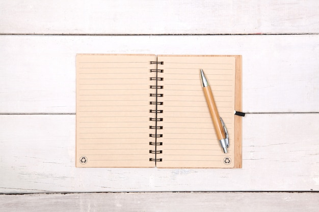 Notebook recycled paper blank on wood table with pen on top.