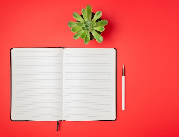 Notebook on a red table. design. minimal concept. flat lay.
