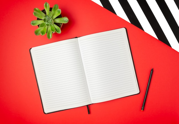 Notebook on a red table. design. minimal concept. flat lay
