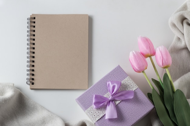 Notebook, scarf, tulips, gift boxes on white surface. spring concept. flat lay, top view