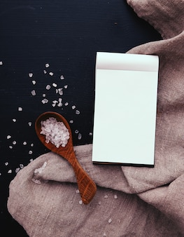 Notebook and sea salt in wooden spoon