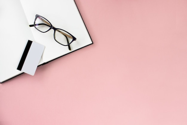 Ноутбук, альбом для рисования, очки, белая карточка на розовом фоне, копией пространства.