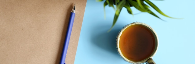 Notebook or sketchbook made of craft paper and a pen and tea cup and green plant on a blue background. banner