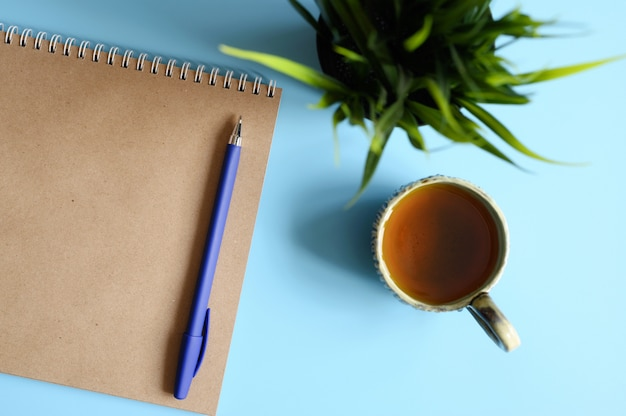 Notebook or sketchbook made of craft paper and a pen and tea cup and green plant