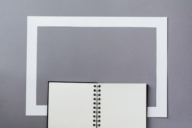 Notebook or sketchbook and paper frame on classic blue background. morning minimal concept. top view with copy space.