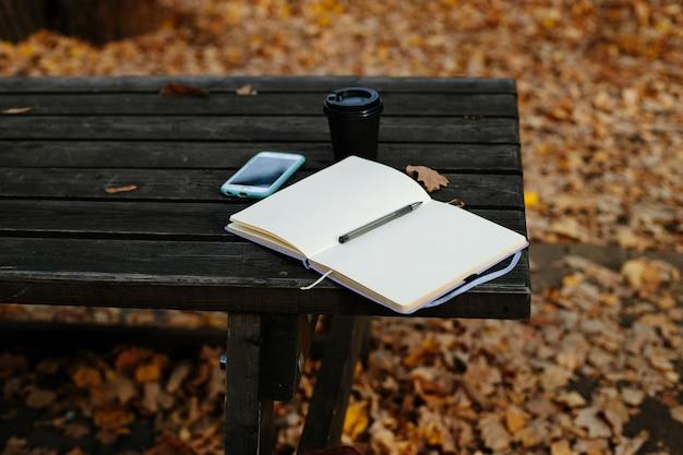 ノートブック、スマートフォン、古い木製のテーブルの上のコーヒー