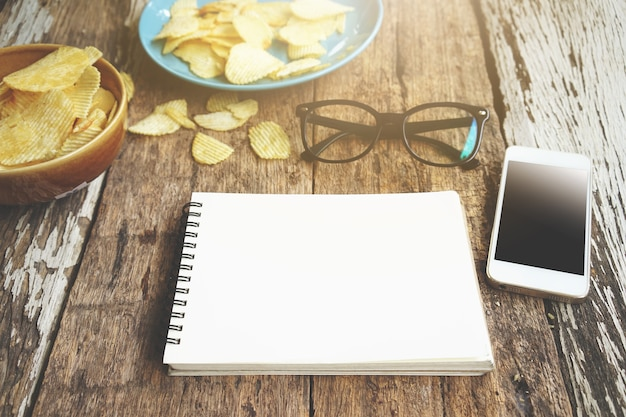 Notebook smartphone glasses and potato chips on work desk