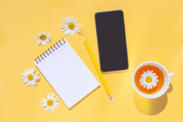 Notebook on a spiral with an empty sheet, a smartphone, a yellow pencil, a cup of tea and chamomile flowers on a bright yellow background.