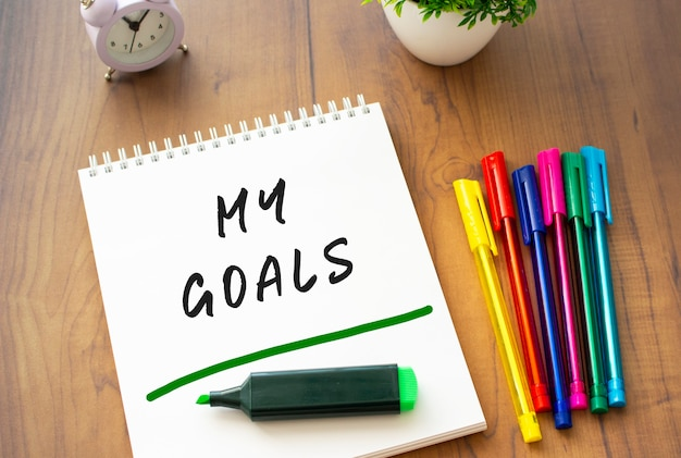 A notebook on a spring with the text my goals on a white sheet lies on a brown wooden table with colored pens. business concept.