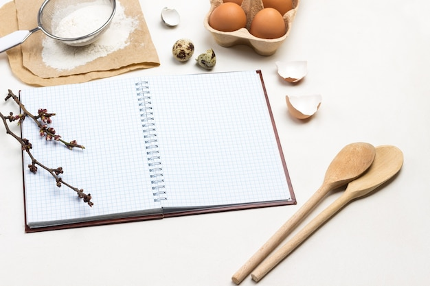 Notebook on springs. two wooden spoons. chicken eggs and chicken shells. flour and sieve on paper. white background. top view.