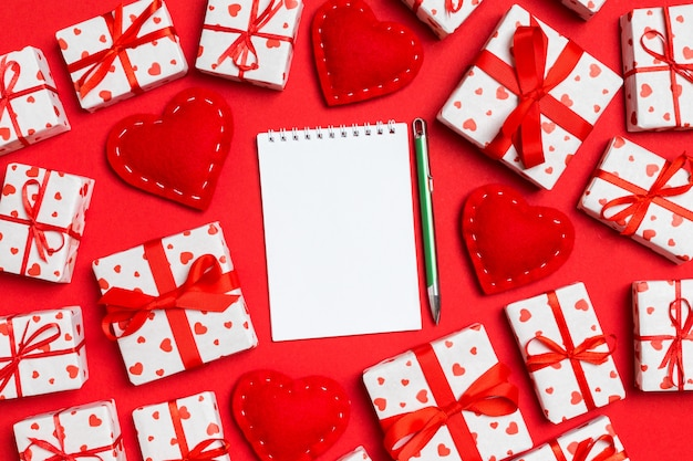 Notebook surrounded by gift boxes with hearts wrapping paper and textile hearts