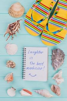 Блокнот опоясан по периметру ракушками и разноцветными туфлями. синий деревянный фон. смех - лучшее лекарство, написанное в блокноте.