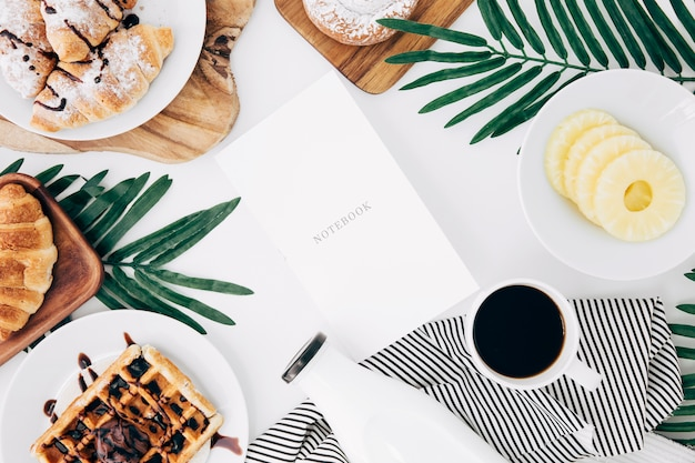 Notebook surrounded with croissant; waffles; pineapple slices; bottle and coffee cup on white backdrop
