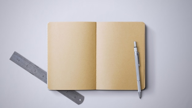Notebook on table with pen and ruler on isolated background