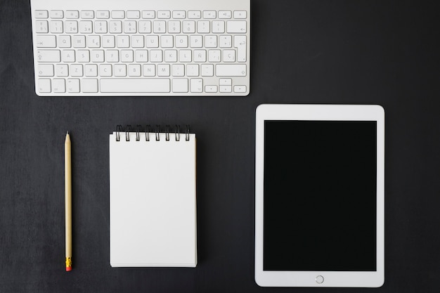 Notebook, tablet and keyboard on dark desk