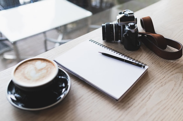 Notebook, vintage camera and hot cappuccino placed on a brown wood table in a coffee shop