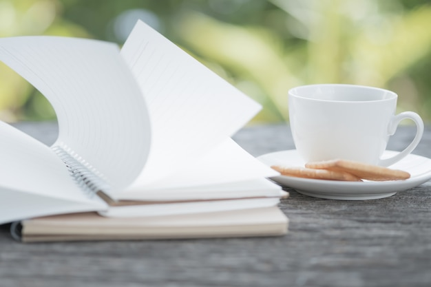 Notebook was blown by wind and coffee cup blur picture