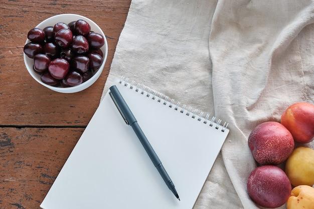 Блокнот с ручкой лежат на скатерти