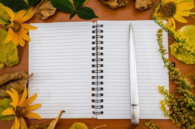 Блокнот с ручкой в осенних желтых листьях и цветах.